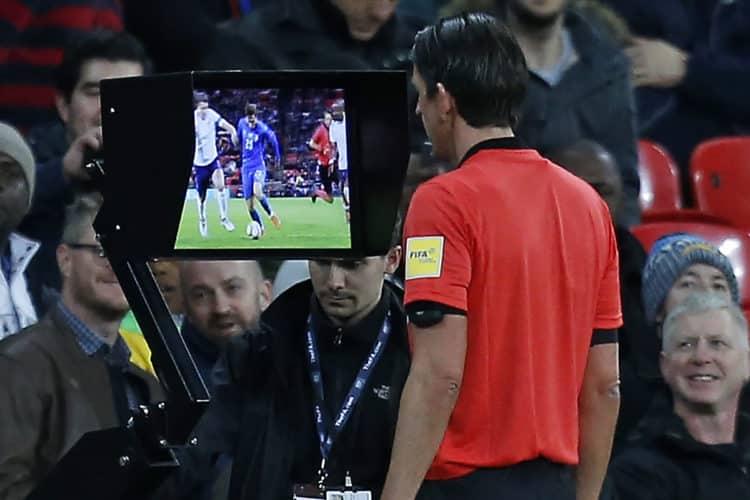 Der deutsche Schiri Deniz Aytekin überprüft eine Szene mit dem VAR (Video Assistant Referee) um festzustellen ob Italien einen Elfmeter hätte bekommen müssen. Spiel zwischen England und Italien im Wembley Stadion in London am 27. März 2018. / AFP PHOTO / Ian KINGTON